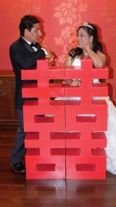 """Purnima and Prasad posed behind a giant Chinese character """"囍"""", which symbolizes the double happiness of the couple."""