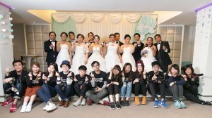 Group photo of Image Pro trainees and ethnic minority couples dressed in wedding gowns and tuxedos.