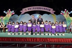 東華三院副主席李鋈麟博士太平紳士(後排右)陪同主禮嘉賓教育局副局長楊潤雄太平紳士(後排左)頒發畢業證書予幼稚園畢業學生代表。