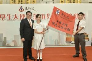 图三为东华三院学生大使三藩市参访团的学生大使代表接受锦旗。