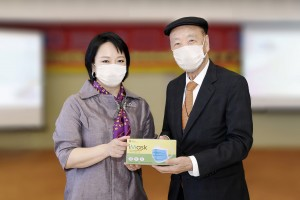 """Ms. Ginny Man (left), the Chairman of TWGHs, offered a box of mask which was the first batch of production, as souvenir to Dr. Lui Che Woo (right), the Chairman of KWIH, to thank him for his donation in setting up """"Medical Mask Production Cleanroom"""" for TWGHs."""