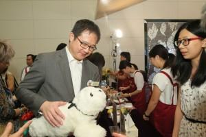 新聞處處長黃智祖太平紳士與電子寵物海豹「東仔」互動。