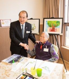 綜合中心94歲高齡的院友黃玉少婆婆(右)向政務司司長張建宗GBS太平紳士(左)介紹其畫作。