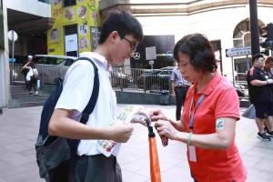 圖十一為義工積極鼓勵市民捐款買旗外,更落力介紹互動遊戲「東華三院X Hello Wong愛‧郵你Action」,籲買旗的市民創作明信片並寫上祝福語或心意字句,以創意傳揚關愛的訊息。
