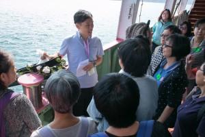 參加者細心聆聽職員講解環保海葬儀式。