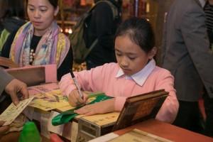 學童幸運抽中「文昌啟智禮」的特別開光紀念福物「文昌絲帶」。