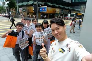 图九为志愿者积极鼓励市民捐款买旗外,更落力介绍互动游戏「『星旗』靓相爱『Fun』享」互动游戏,东华三院主席王贤志先生亦响应呼吁与卖旗志愿者拍下一张爱心爆棚的相片。
