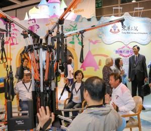 家庭議會主席石丹理教授SBS太平紳士(右)參觀東華三院的攤位,了解多功能運動儀器如何提升長者身體各部份肌肉的持久力。