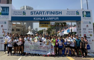 東華三院iRun跑手及伴跑員在「2019吉隆坡渣打馬拉松」起步拱門前合照